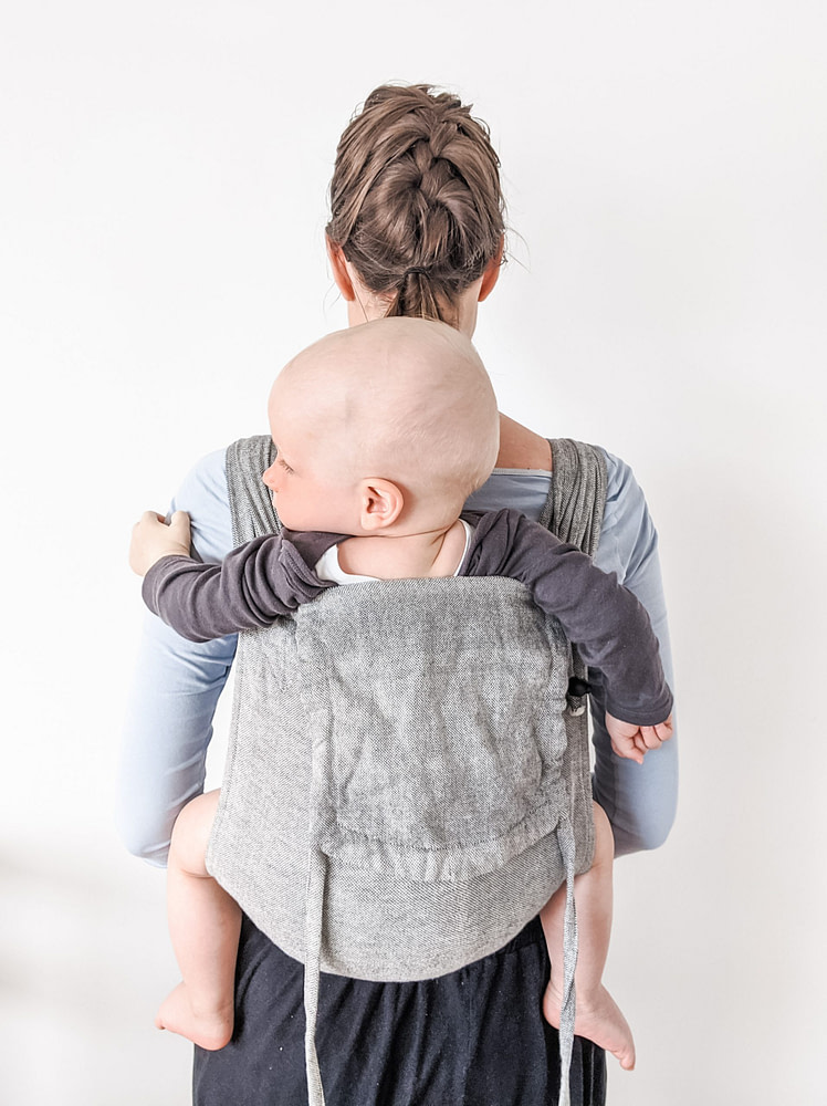 Mom wearing baby on her back in a Girasol Mywrapsol wrap conversion meh dai baby carrier