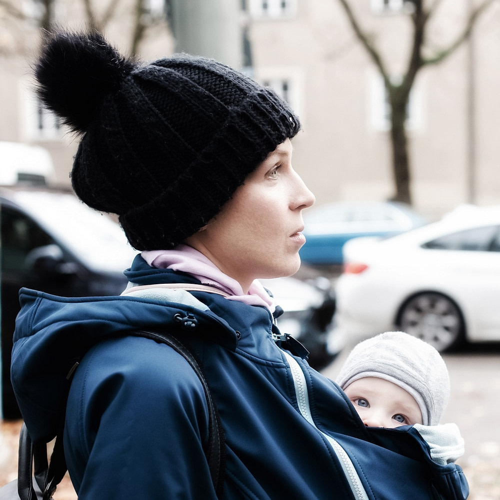 Babywearing mom carrying her baby under a babywearing jacket