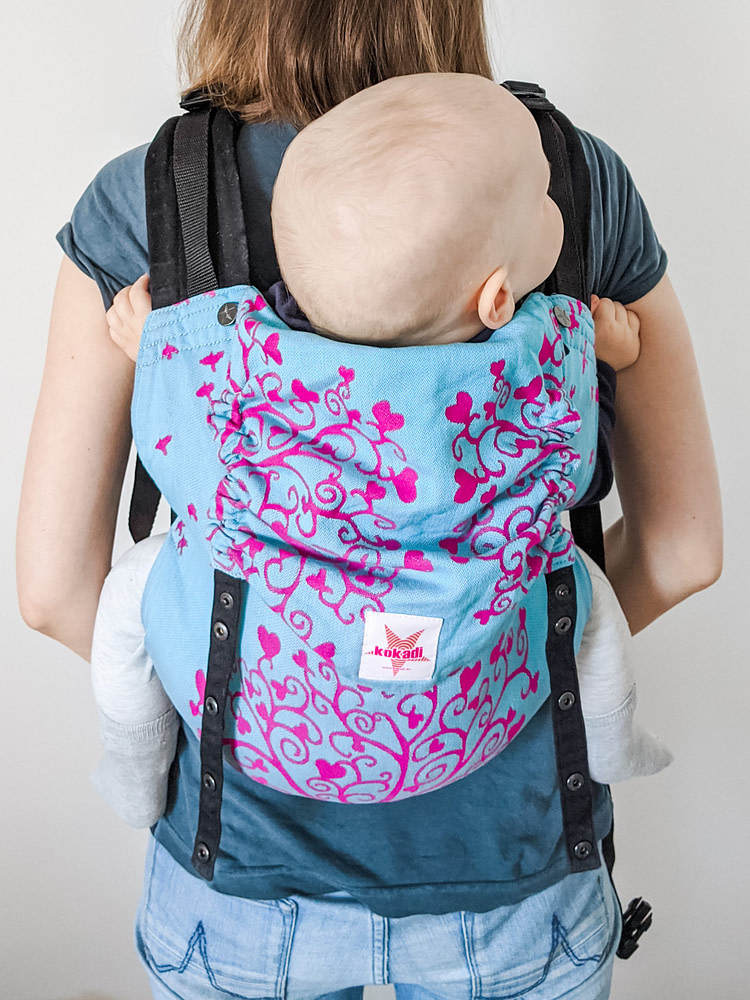 Mom wearing her baby in a full buckle baby carrier on her back