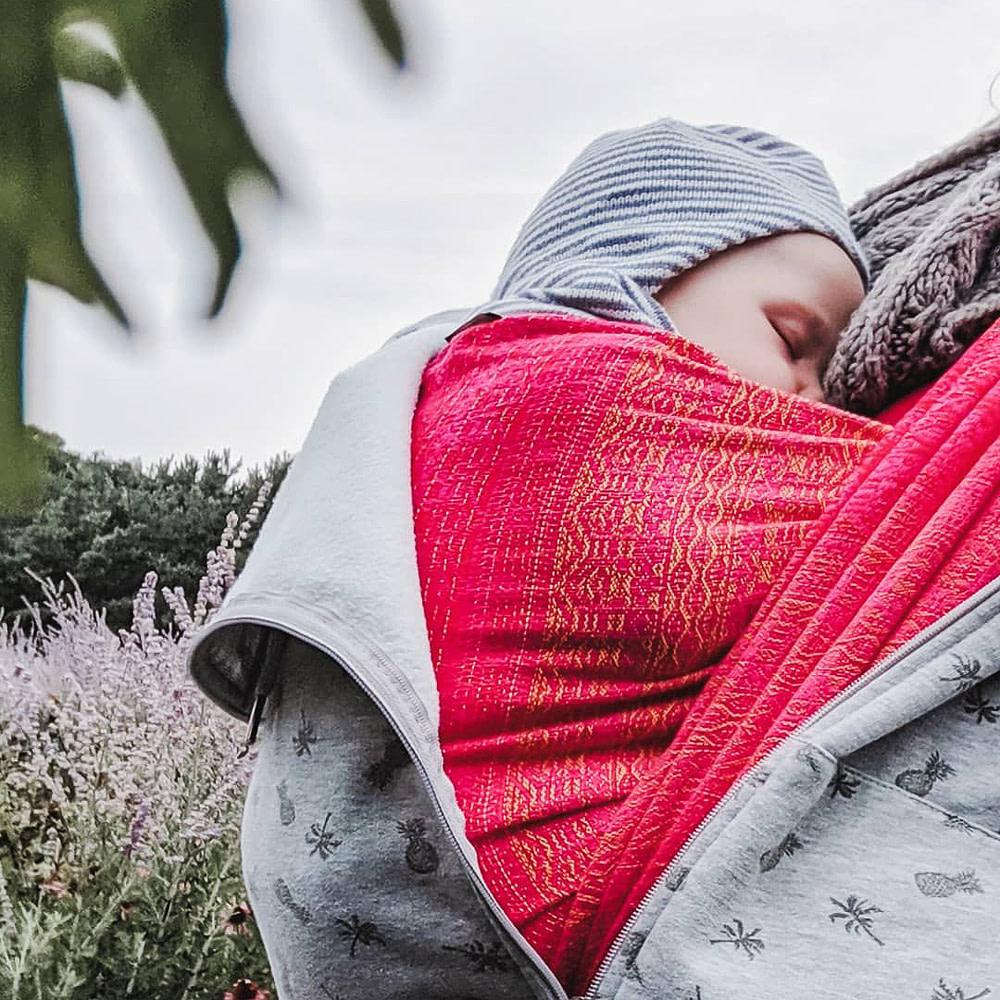 Sleeping baby carried in a pink babywearing wrap.